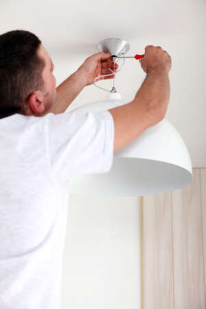 Man fixing ceiling light photo