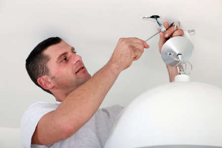 light fitting: Man fixing light at home Stock Photo
