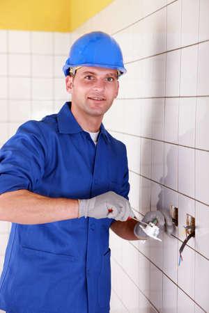Electrician fixing bathroom socket photo