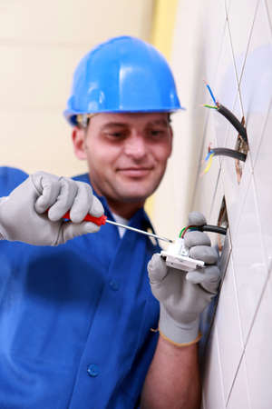 wall socket: Electrician wiring a wall socket