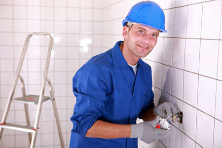 light fitting: Electrician fitting a light switch in a large white tiled room Stock Photo
