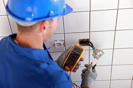wall socket: Electrician checking the wiring of a wall socket