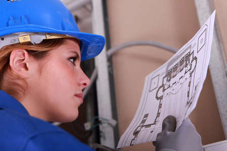 mechanical engineering: Female electrician reading diagram Stock Photo