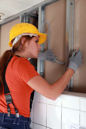 Female electrician working on wiring photo