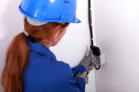 Young woman fitting an electrical socket photo