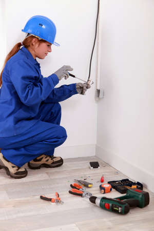 Woman fixing house electrics photo