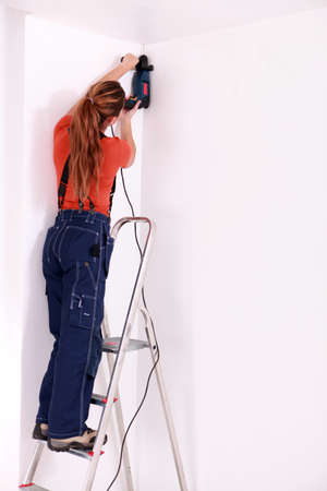 electric drill: Female drilling roof