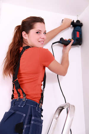 Woman drilling roof Stock Photo - 13782865