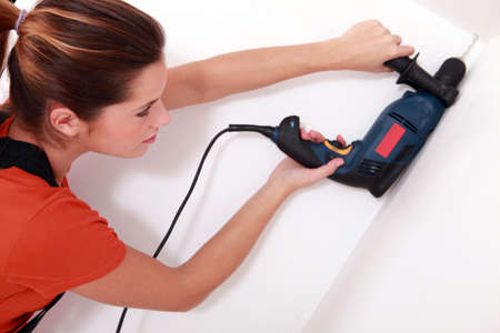 handywoman drilling a hole in the ceiling Stock Photo - 13782826