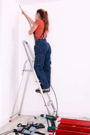 electric drill: Woman wiring a room