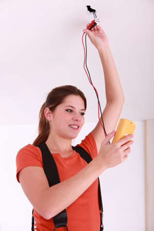 voltmeter: Woman using a voltmeter on ceiling electrics