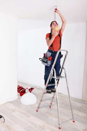 fixate: Handywoman fixate a lamp on the ceiling Stock Photo