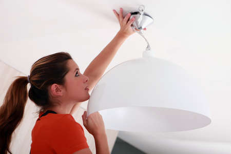 placing: Woman placing a lamp in the ceiling