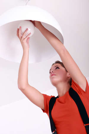Woman fixing ceiling light photo