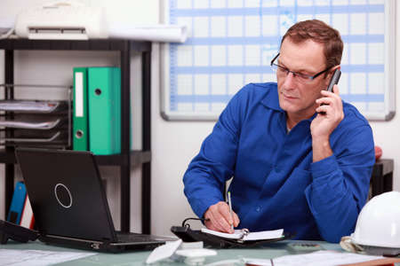 blue collar: Mechanic on phone in office