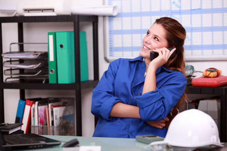 wholesale: Young woman in blue overalls on the telephone in a depot