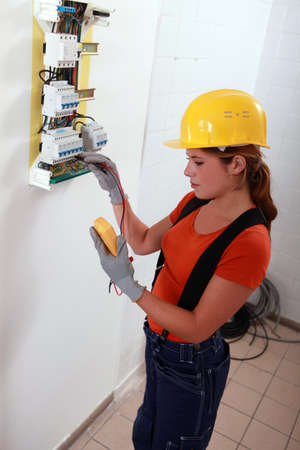 fuse box: Female electrician with a fuse box Stock Photo
