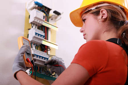 electrician: Woman measuring electrical current Stock Photo