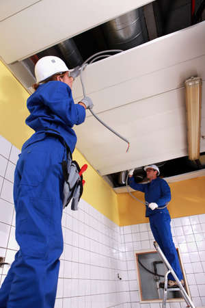 Two electrician repairing ceiling lighting photo