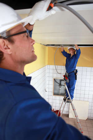 Laborers installing piping in ceiling photo
