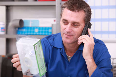 plumbing supply: Plumbers merchant on the phone with a part in hand