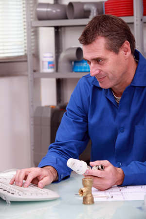 plumbing supply: Plumber in a shop checking details of a thermostatic valve on a computer Stock Photo