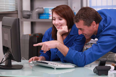 young engineer: two colleagues in blue jumpsuit watching a computer Stock Photo