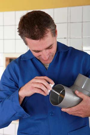 lubrication: Plumber preparing plastic pipe Stock Photo