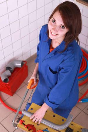 Woman sawing tube photo