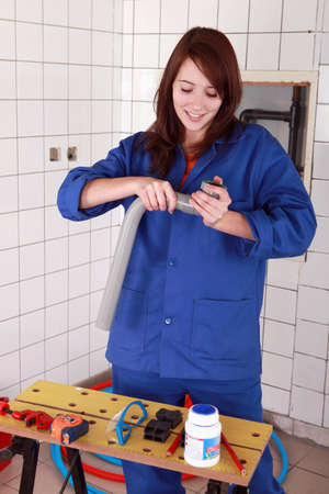 tradesperson: Female plumber putting plastic pipes together