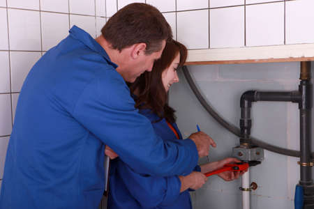 female apprentice plumber and male instructor photo