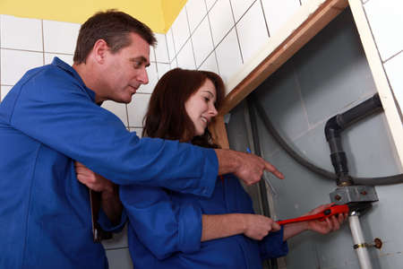 instructing: Plumber instructing his apprentice Stock Photo