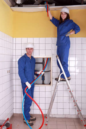 ladder safety: Electricians man and woman Stock Photo
