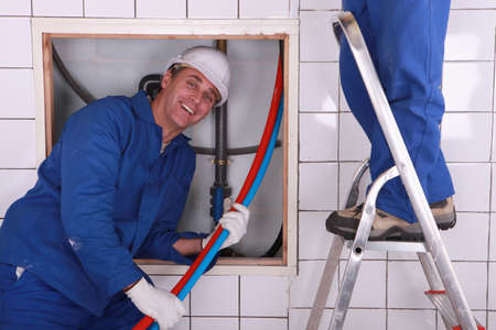 tradespeople: Workers installing a water system Stock Photo