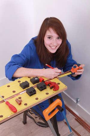 koperen leiding: Vrouw meten van een koperen buis Stockfoto