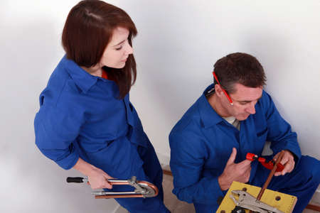 practical: Plumber cutting copper pipe while his female apprentice watches