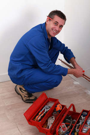 Plumber kneeling by tool box photo