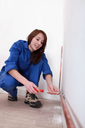 Tradeswoman fixing a copper tube against a wall Stock Photo - 13783056
