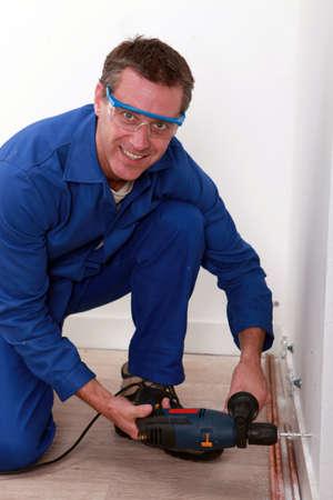 hunker: plumbing wearing goggles using drill Stock Photo