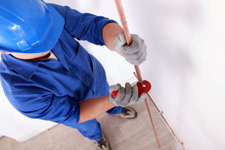 Worker cutting a copper tube Stock Photo - 13783285