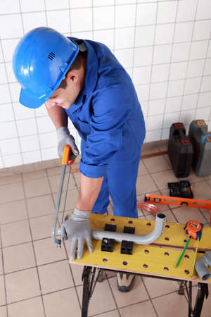 Plumber cutting grey plastic pipe photo