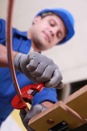 koperen leiding: Arbeider met behulp van gereedschap om koperen buis voor te bereiden Stockfoto