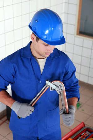 koperen leiding: Loodgieter buigen koperen buis Stockfoto