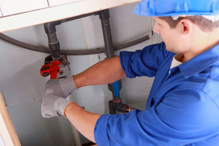 Plumber installing pipes photo