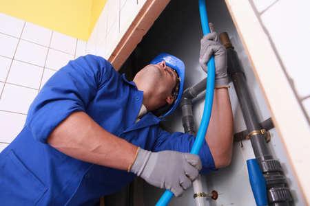 piping: Plumber pulling tube