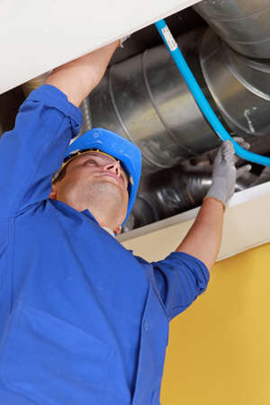 air duct: Plumber holding a blue flexible pipe under some air ducts