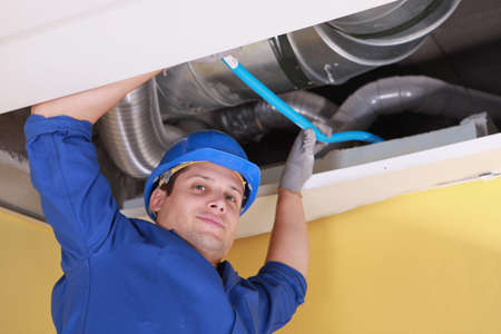 air duct: Plumber holding a blue pipe above a ceiling