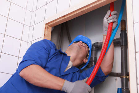flexi: Plumber feeding flexible pipes behind a tiled wall Stock Photo