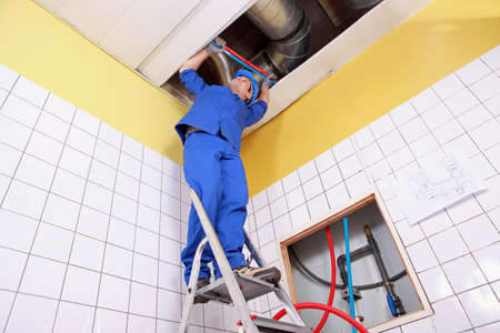 ladder safety: Plumber working on a ladder Stock Photo