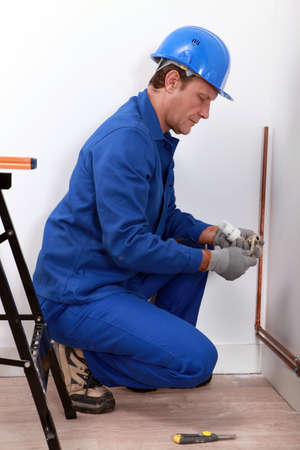 Construction worker installing a pipe photo